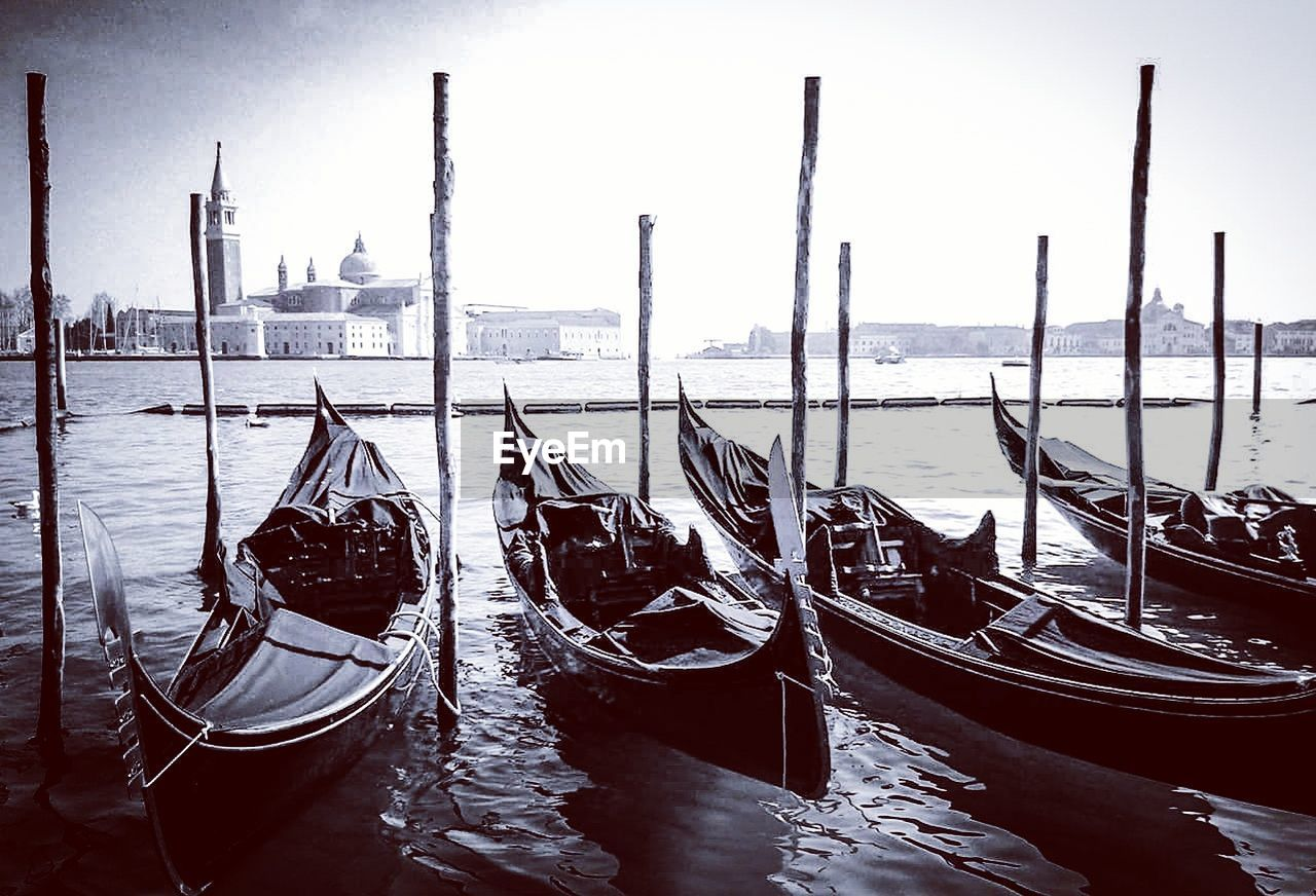 water, architecture, moored, built structure, transportation, no people, gondola, day, building exterior, waterfront, gondola - traditional boat, nautical vessel, wooden post, travel destinations, sky, outdoors, nature