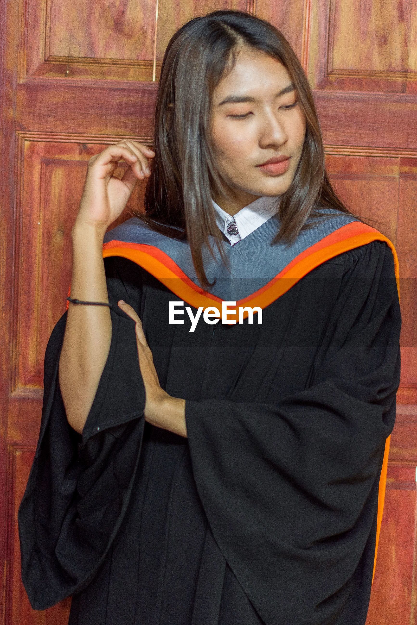 Thoughtful young woman in graduation gown standing door