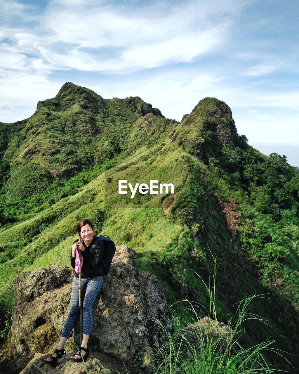 Female hiker sitting on mountain against sky