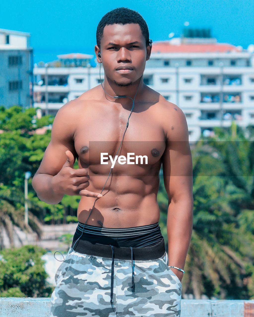 one person, standing, young adult, lifestyles, front view, real people, shirtless, muscular build, young men, architecture, focus on foreground, building exterior, nature, day, built structure, leisure activity, three quarter length, looking at camera, beautiful people, outdoors