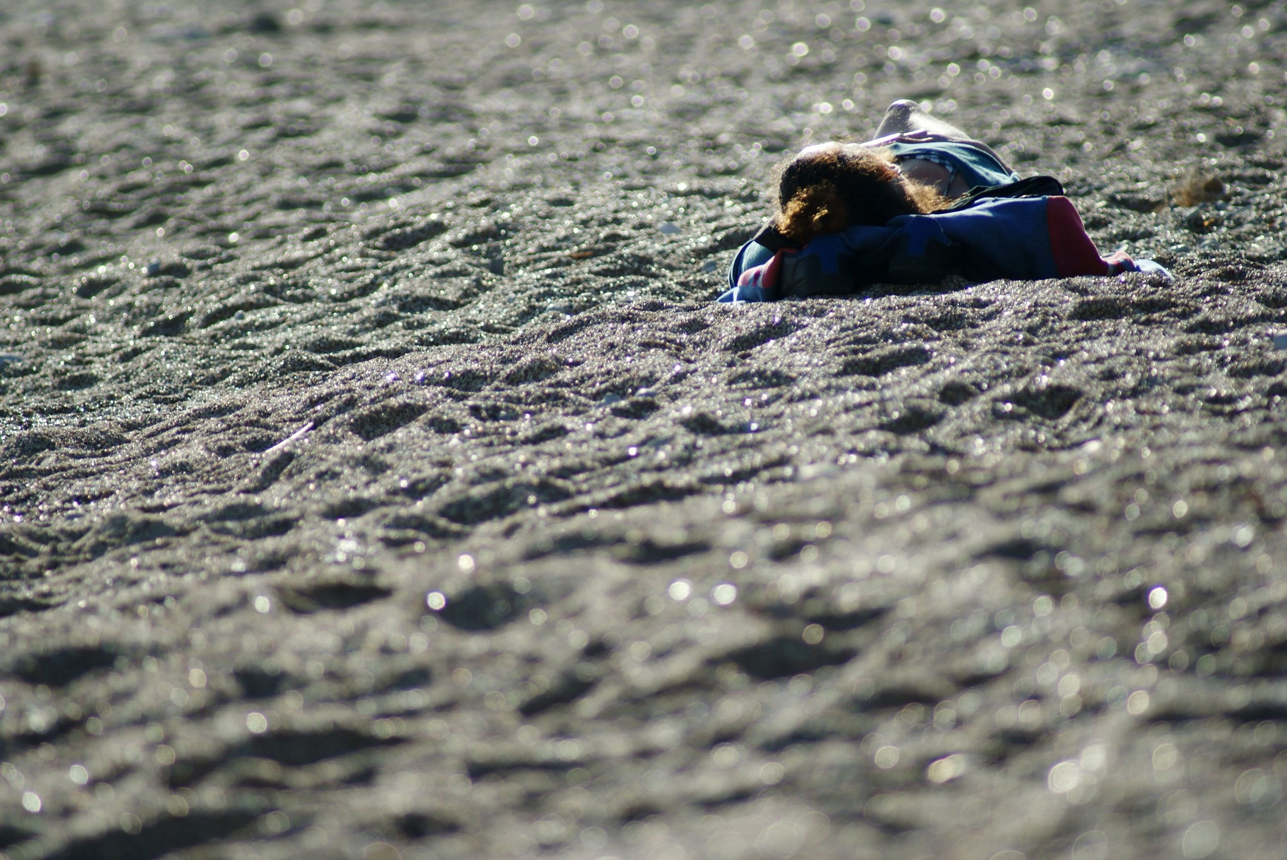 Surface level of woman lying on sand