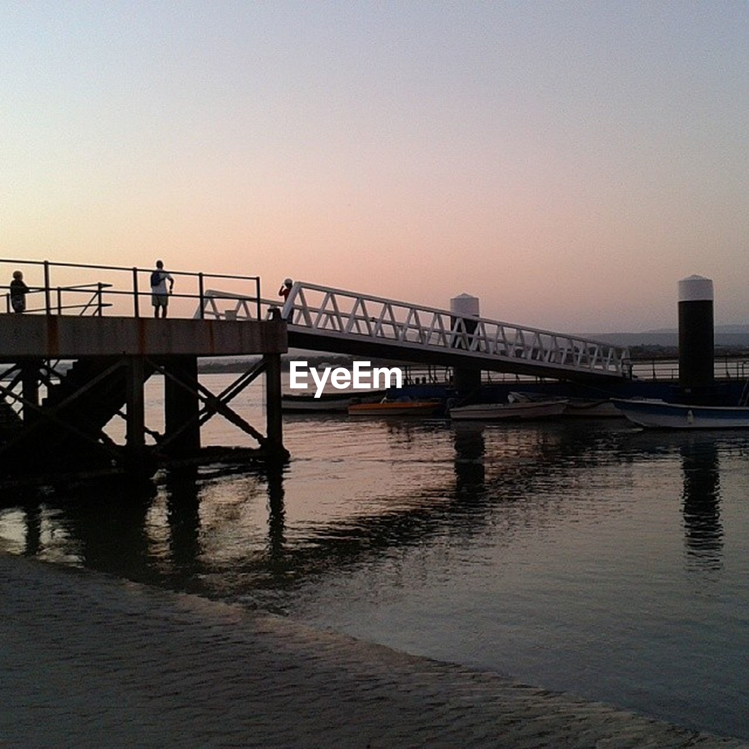 water, clear sky, sunset, built structure, copy space, architecture, bridge - man made structure, connection, pier, silhouette, river, railing, sea, bridge, tranquility, reflection, waterfront, nature, transportation, tranquil scene