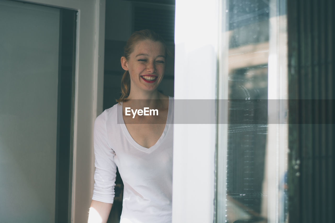 Cheerful Woman Standing By Windows On Sunny Day