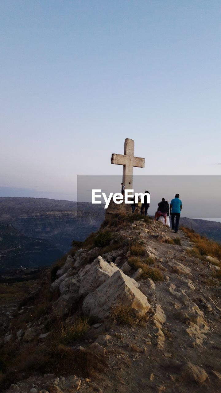 spirituality, real people, religion, cross, rock - object, nature, outdoors, mountain, sky, scenics, day, tranquility, women, beauty in nature, men, clear sky, lifestyles, travel destinations, landscape, people