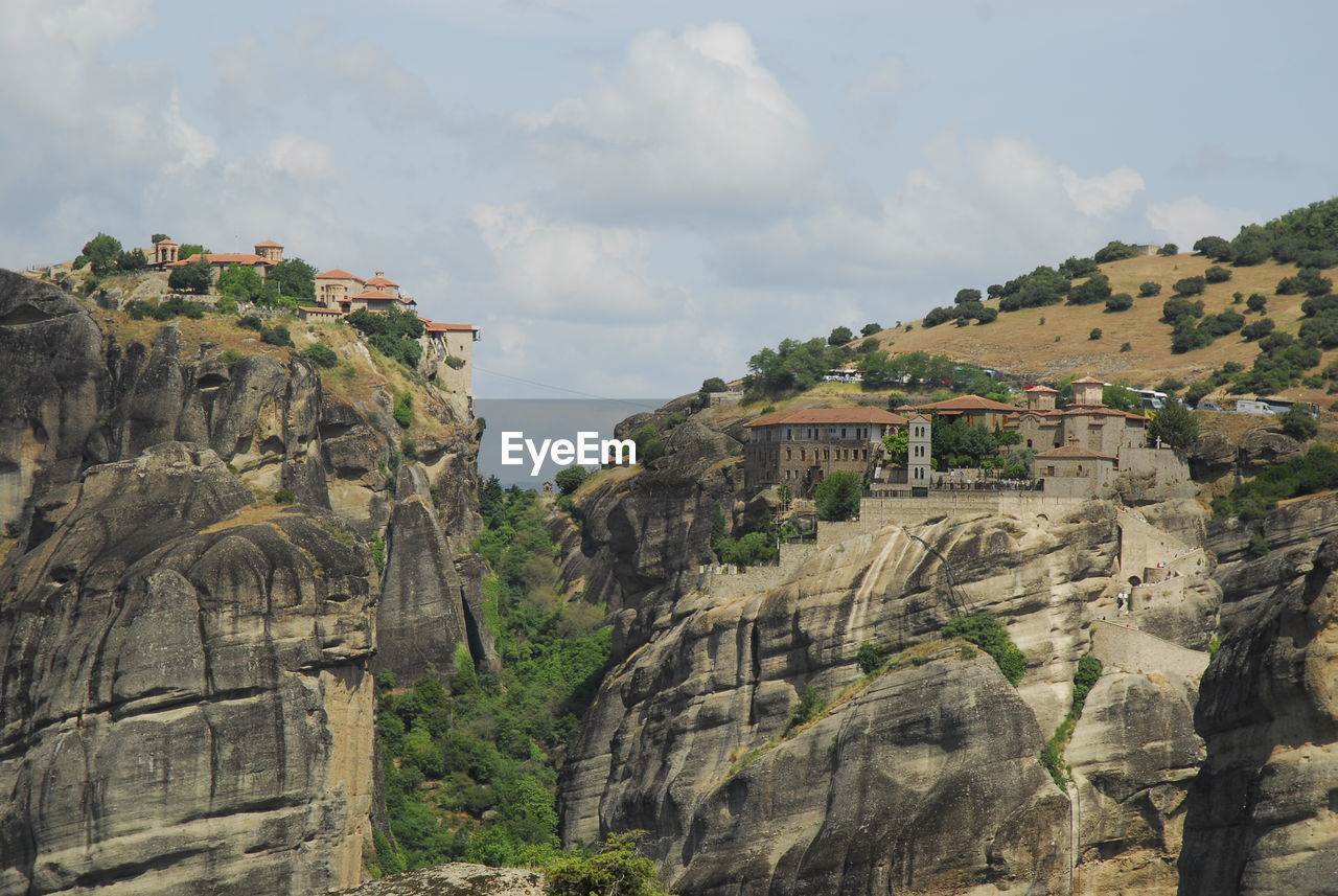 PANORAMIC VIEW OF BUILDINGS AND ROCK FORMATIONS AGAINST SKY