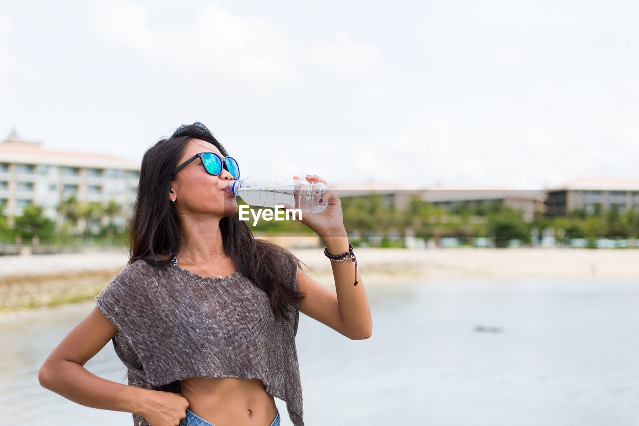 Young Woman Drinking Water At Beach Against Sky