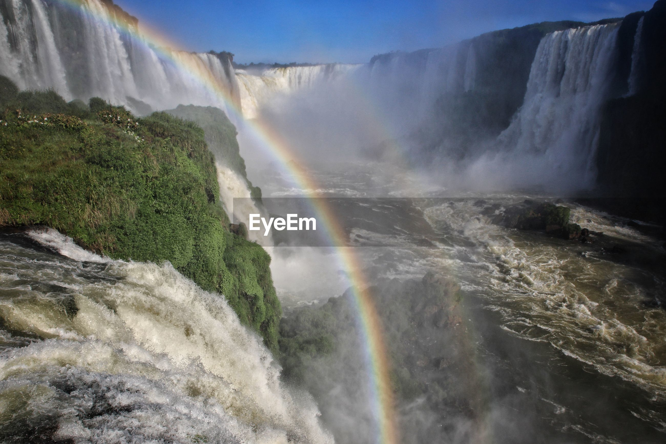 SCENIC VIEW OF WATERFALL AGAINST RAINBOW