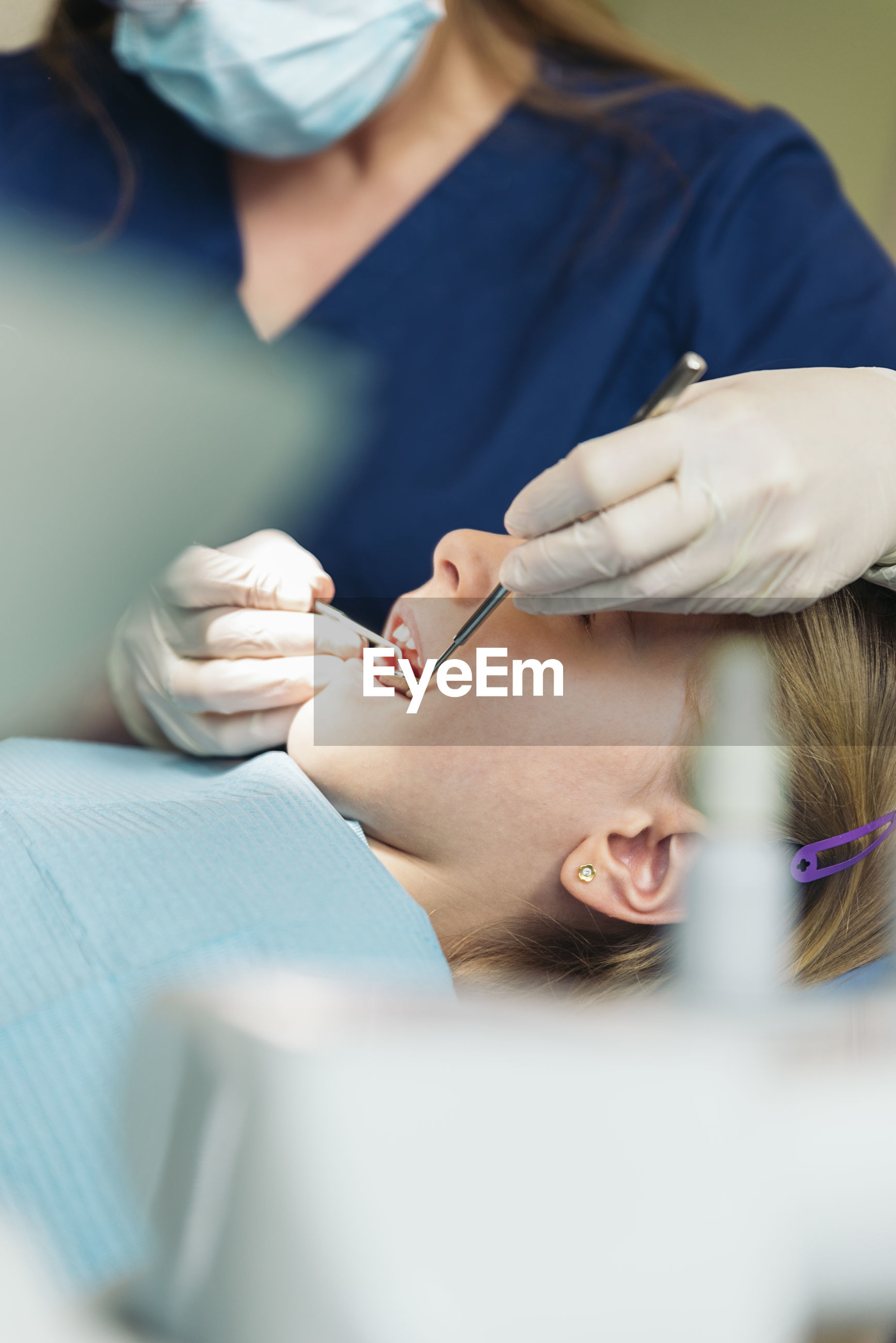 Female dentist examining girl at clinic