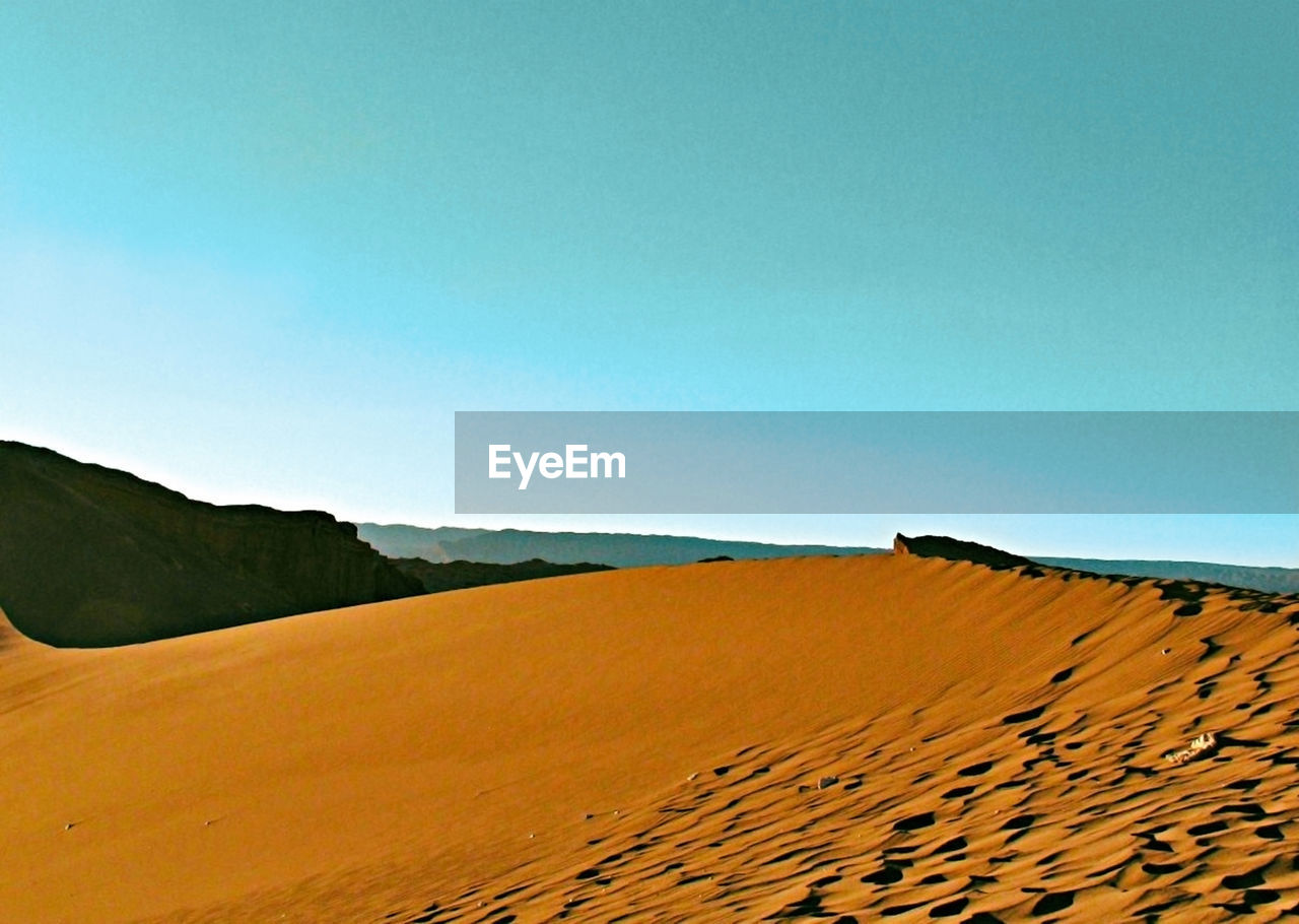 sky, scenics - nature, clear sky, landscape, copy space, tranquil scene, blue, tranquility, land, beauty in nature, nature, environment, desert, non-urban scene, day, sand, sand dune, no people, mountain, climate, arid climate, outdoors, atmospheric
