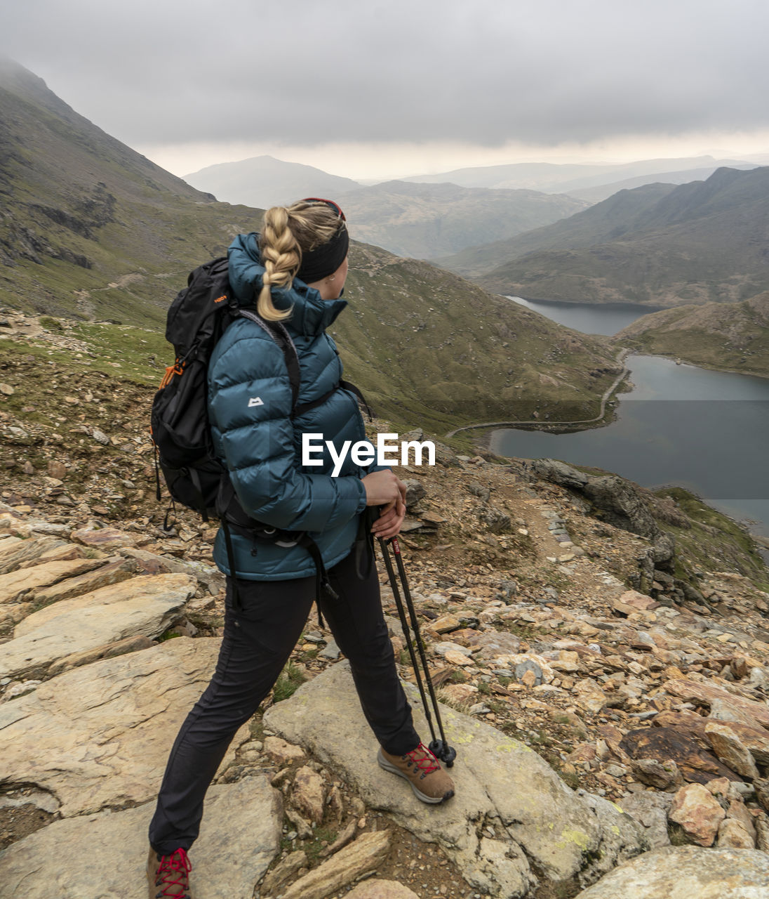 mountain, real people, leisure activity, lifestyles, beauty in nature, scenics - nature, full length, water, one person, sky, nature, non-urban scene, tranquility, tranquil scene, hiking, activity, day, environment, mountain range, outdoors, warm clothing