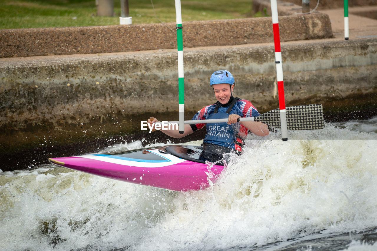 Young woman kayaking on river