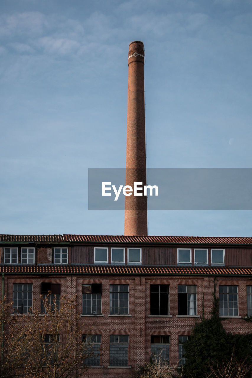 building exterior, architecture, built structure, sky, smoke stack, factory, nature, no people, industry, day, pollution, low angle view, building, chimney, outdoors, cloud - sky, environmental issues, tall - high, smoke - physical structure, air pollution