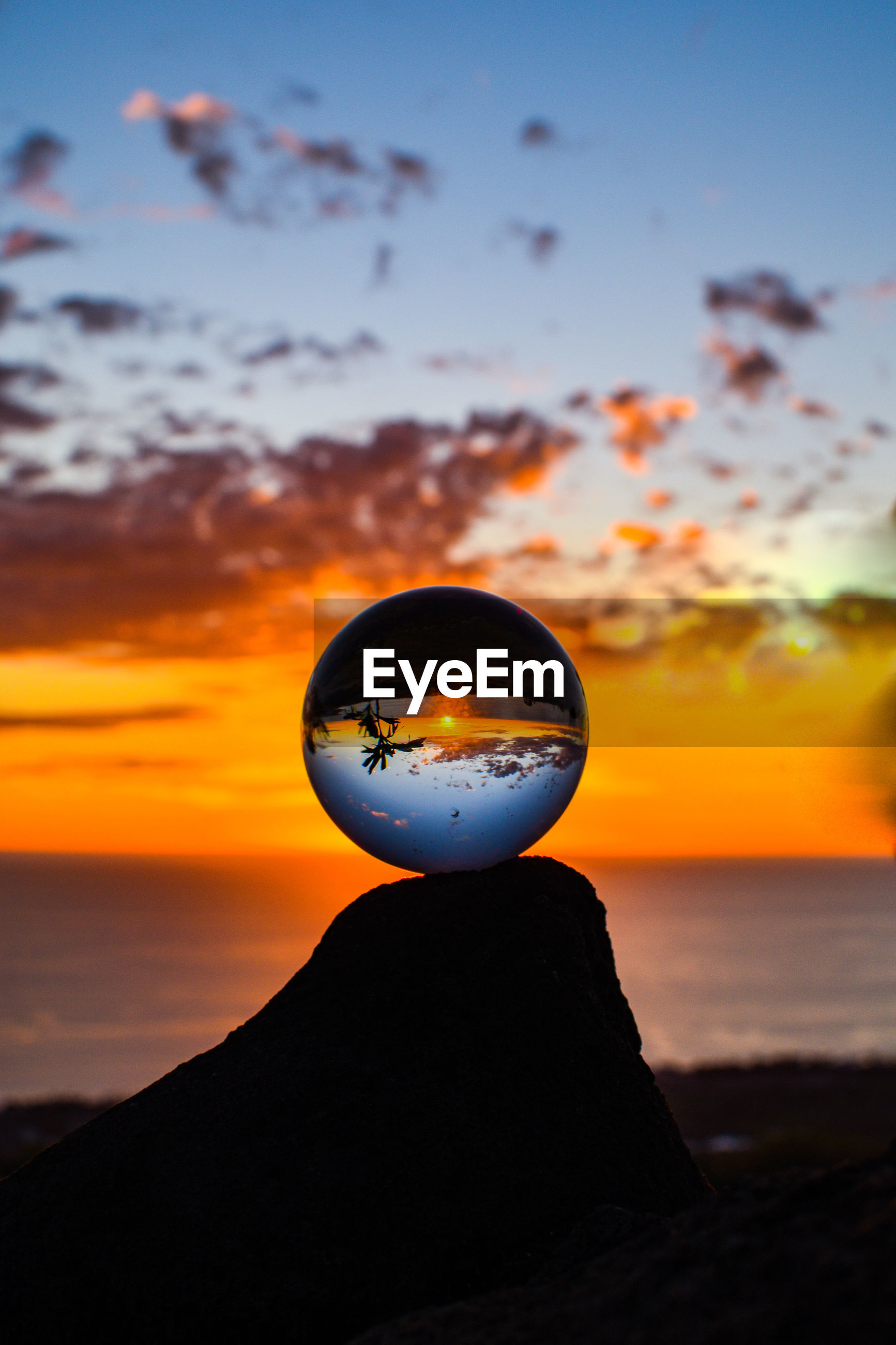 Crystal ball with sea and cloudy sky reflection during sunset