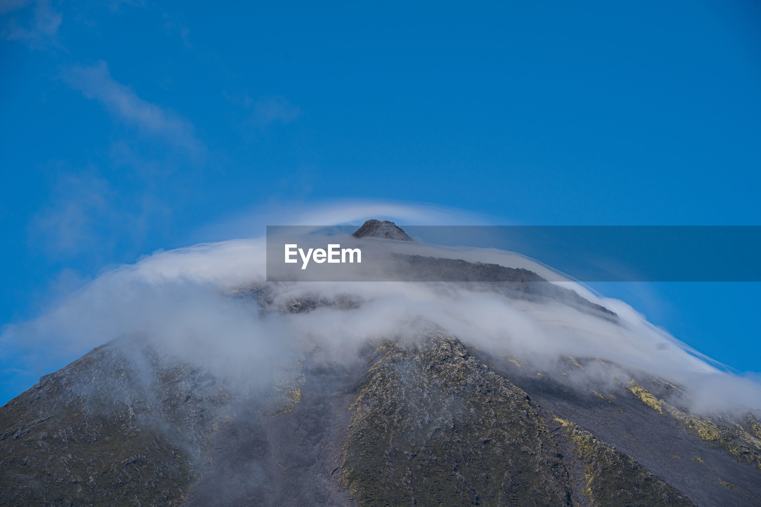 AERIAL VIEW OF VOLCANIC MOUNTAIN AGAINST BLUE SKY