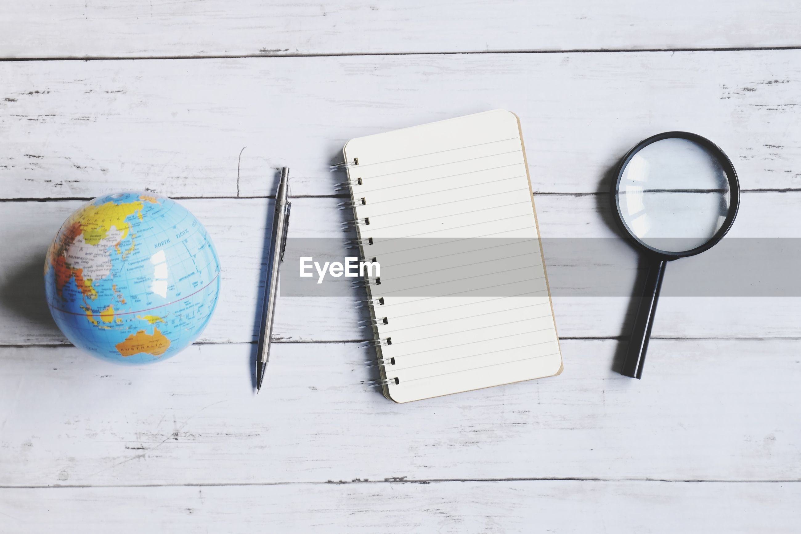 Directly above shot of spiral notebook with pen and globe on wooden table