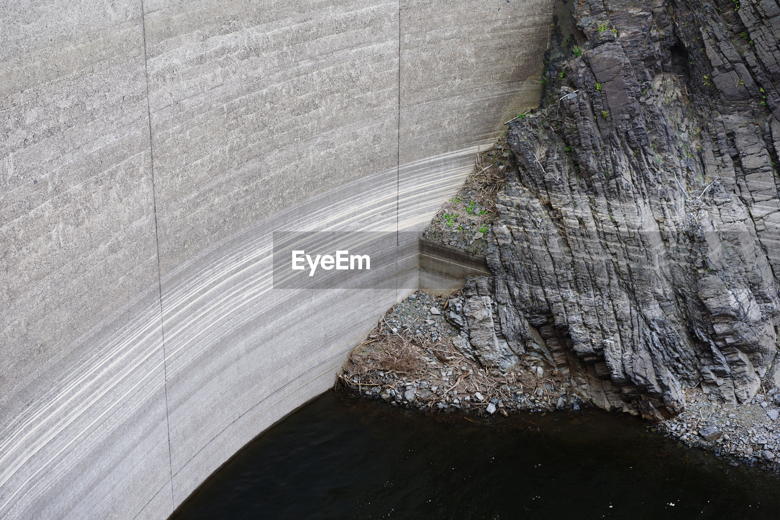 High angle view of water in a dam, with the dam wall and rocks showing water evaporation levels