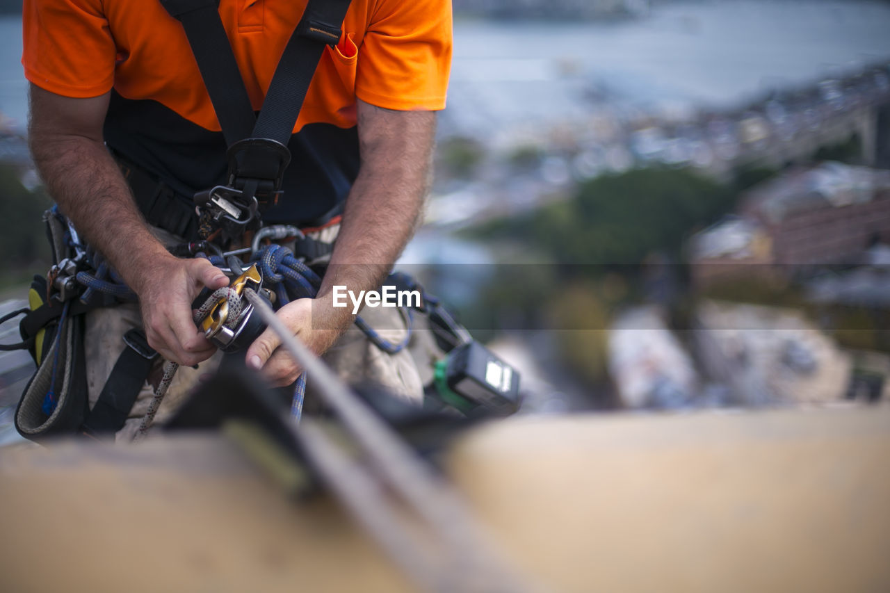 one person, real people, midsection, men, working, holding, selective focus, occupation, transportation, day, front view, outdoors, mode of transportation, sport, standing, nature, lifestyles, metal