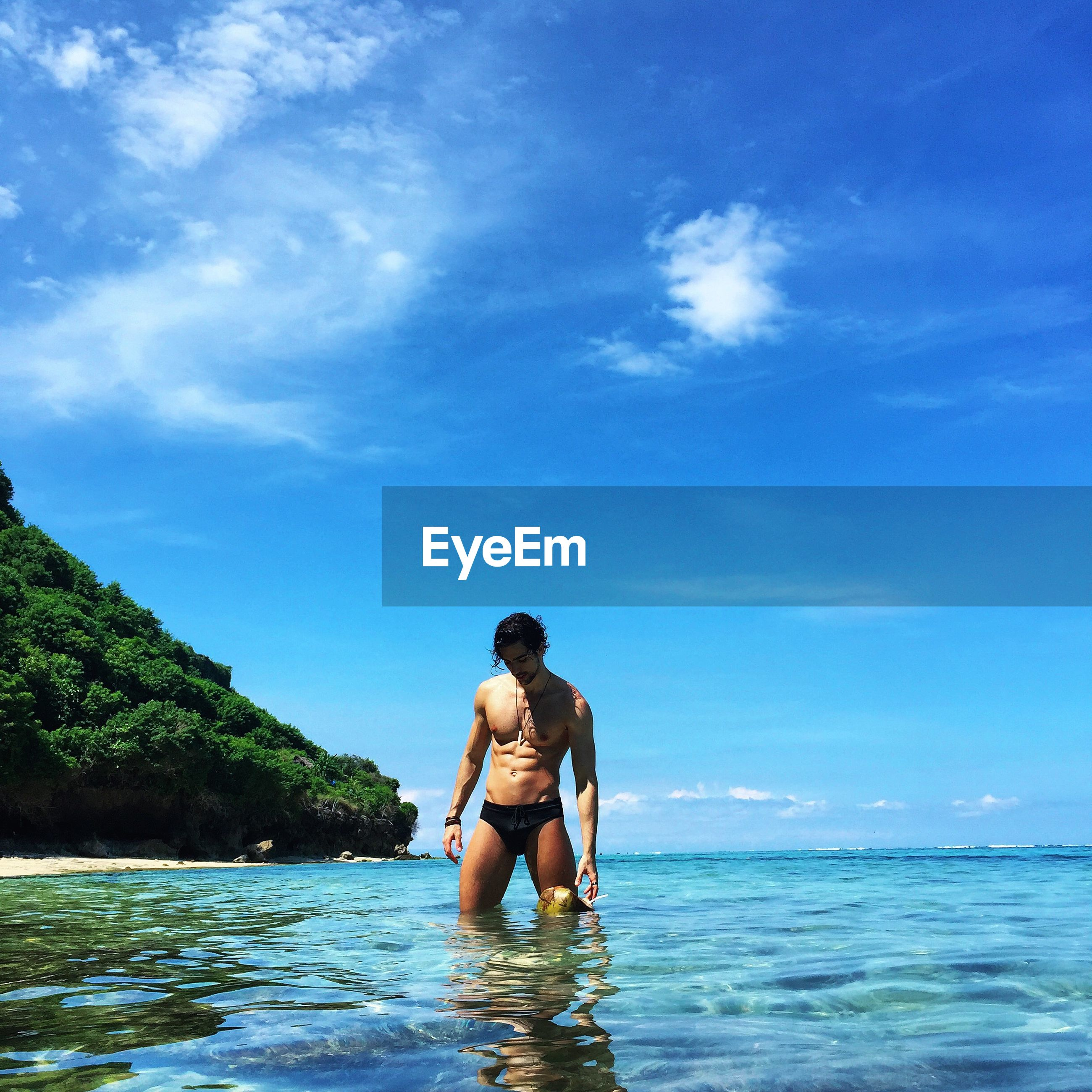 water, leisure activity, lifestyles, sea, sky, vacations, full length, young adult, blue, waterfront, shirtless, person, casual clothing, rear view, nature, beauty in nature, scenics, young men