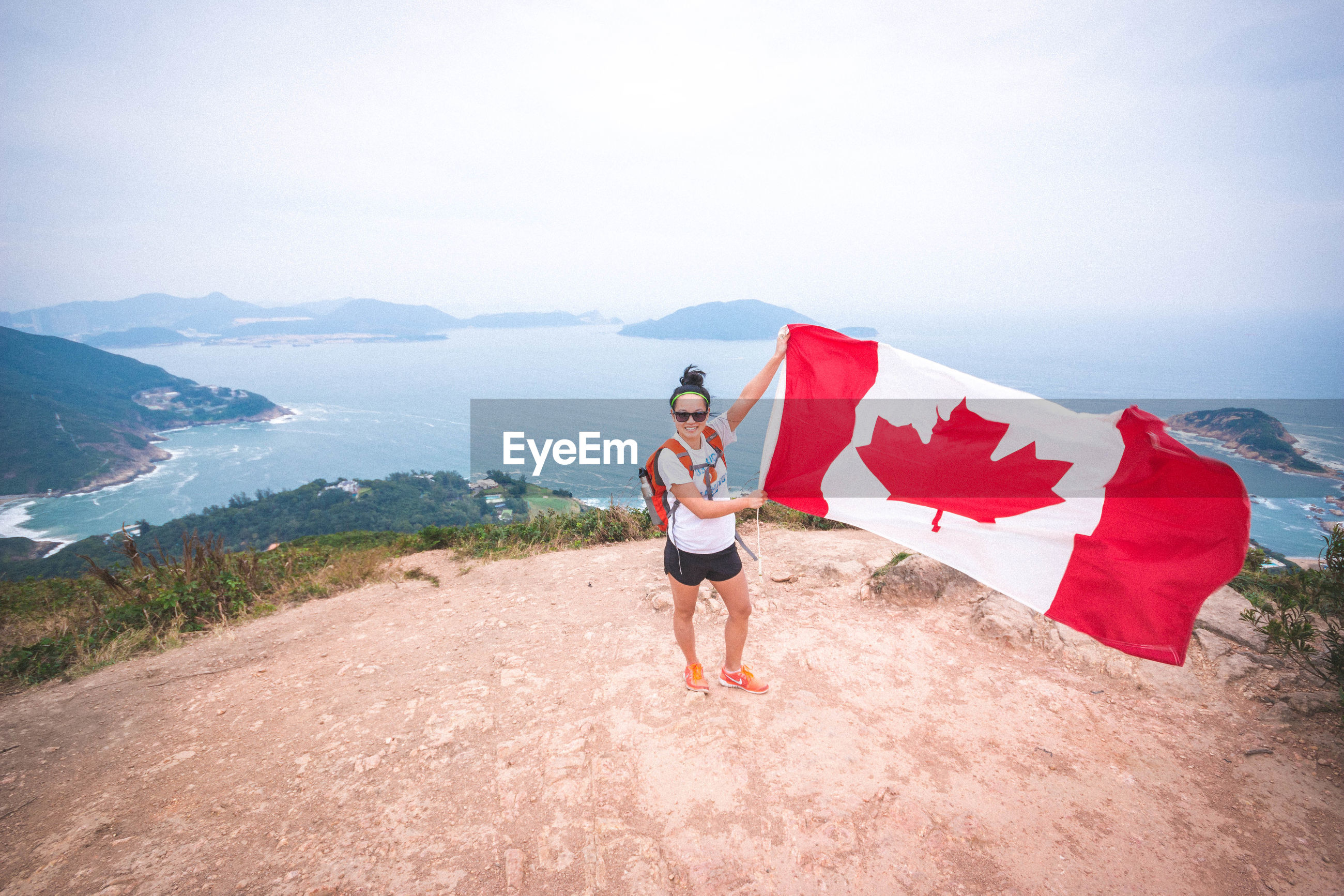 High angle view of excited woman holding canadian flag at dragons back mountain peak against sea