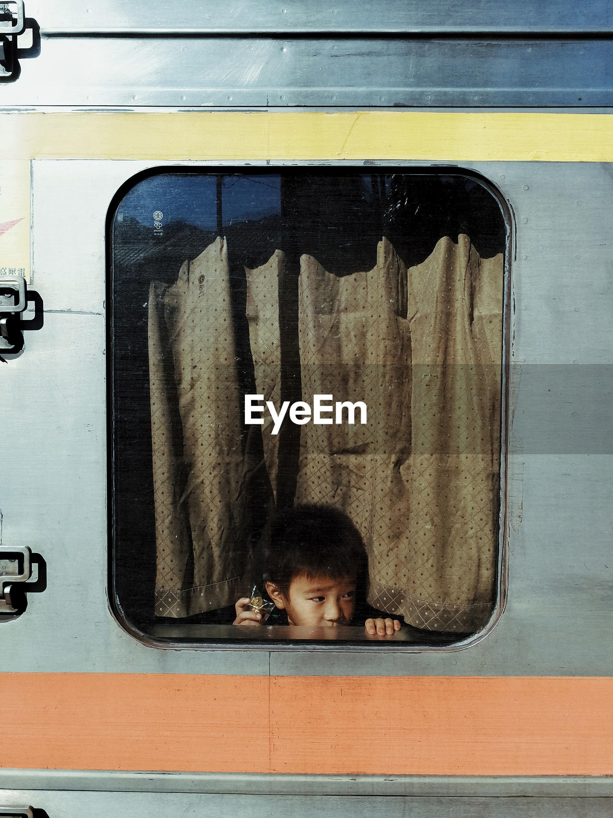 Boy looking away through train window