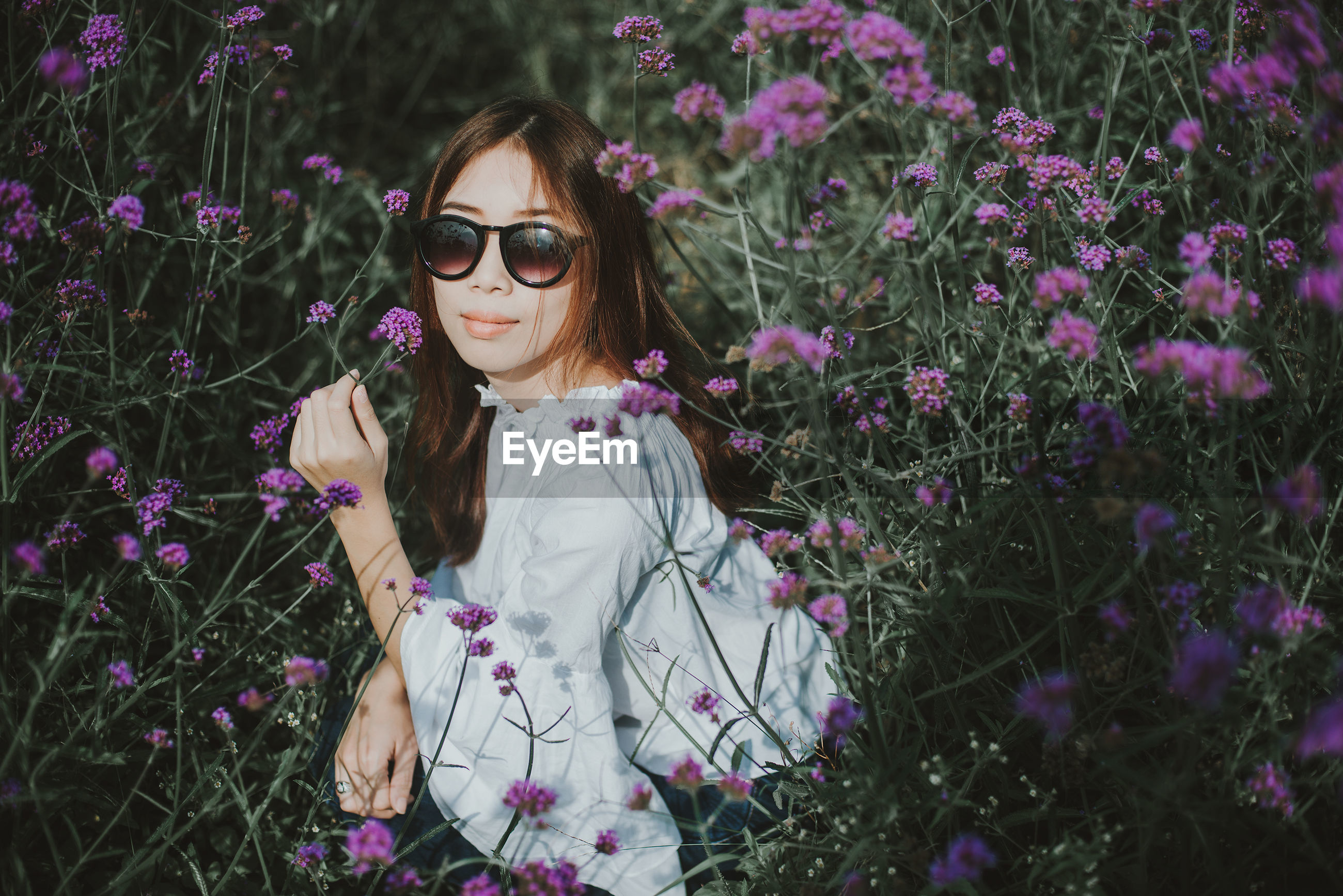 Portrait of young woman amidst flowering plants