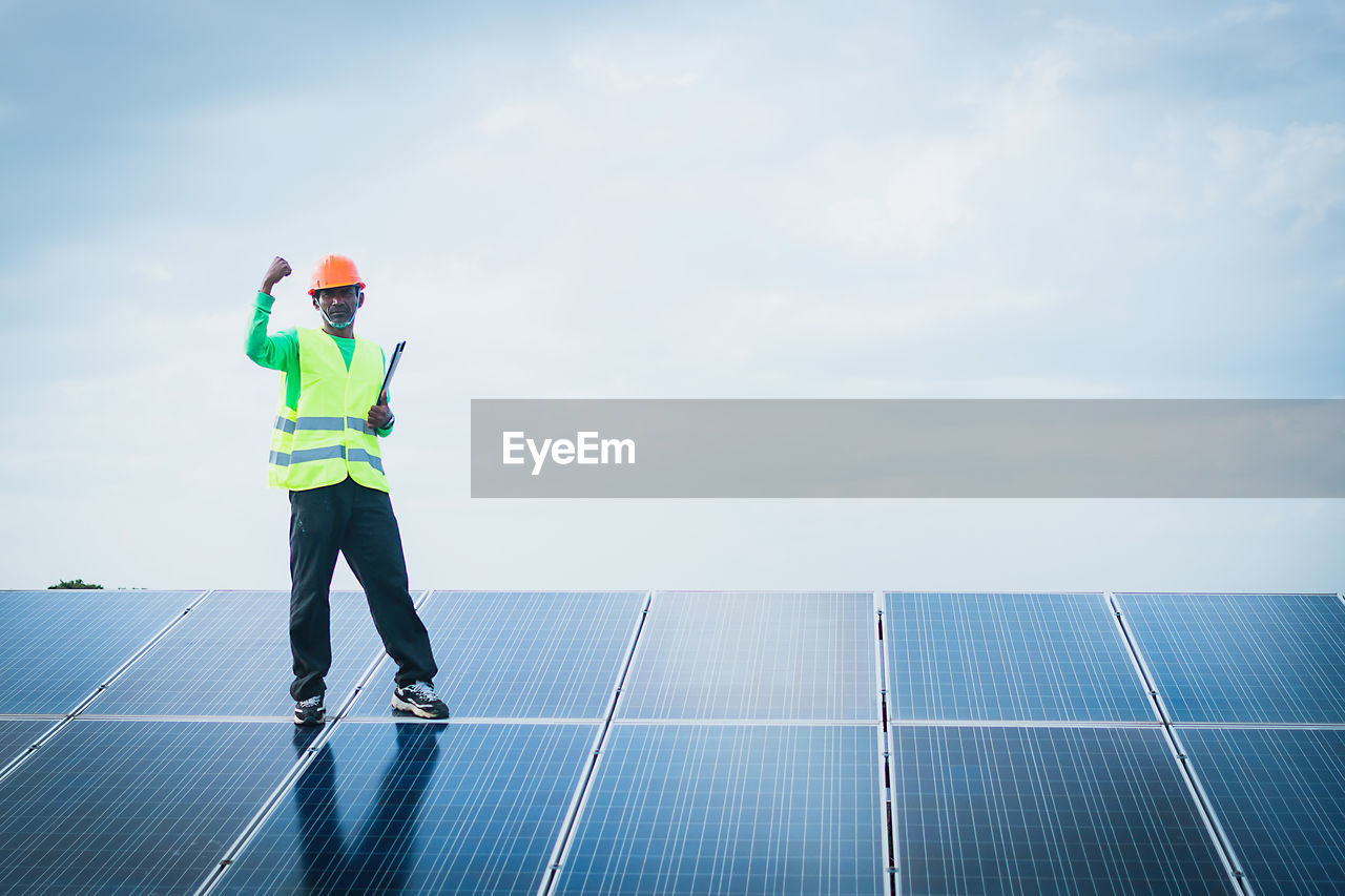 sky, cloud - sky, full length, reflective clothing, one person, real people, nature, occupation, men, safety, helmet, day, renewable energy, environment, solar energy, clothing, solar panel, alternative energy, headwear, outdoors, sustainable resources