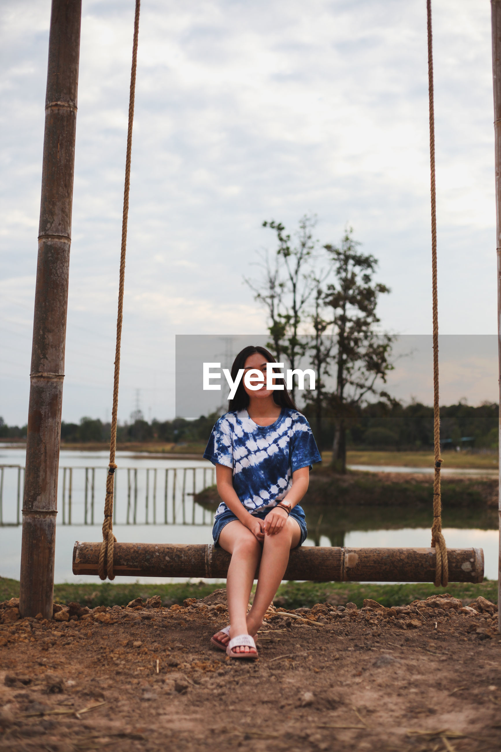 Full length portrait of young woman sitting by lake on swing