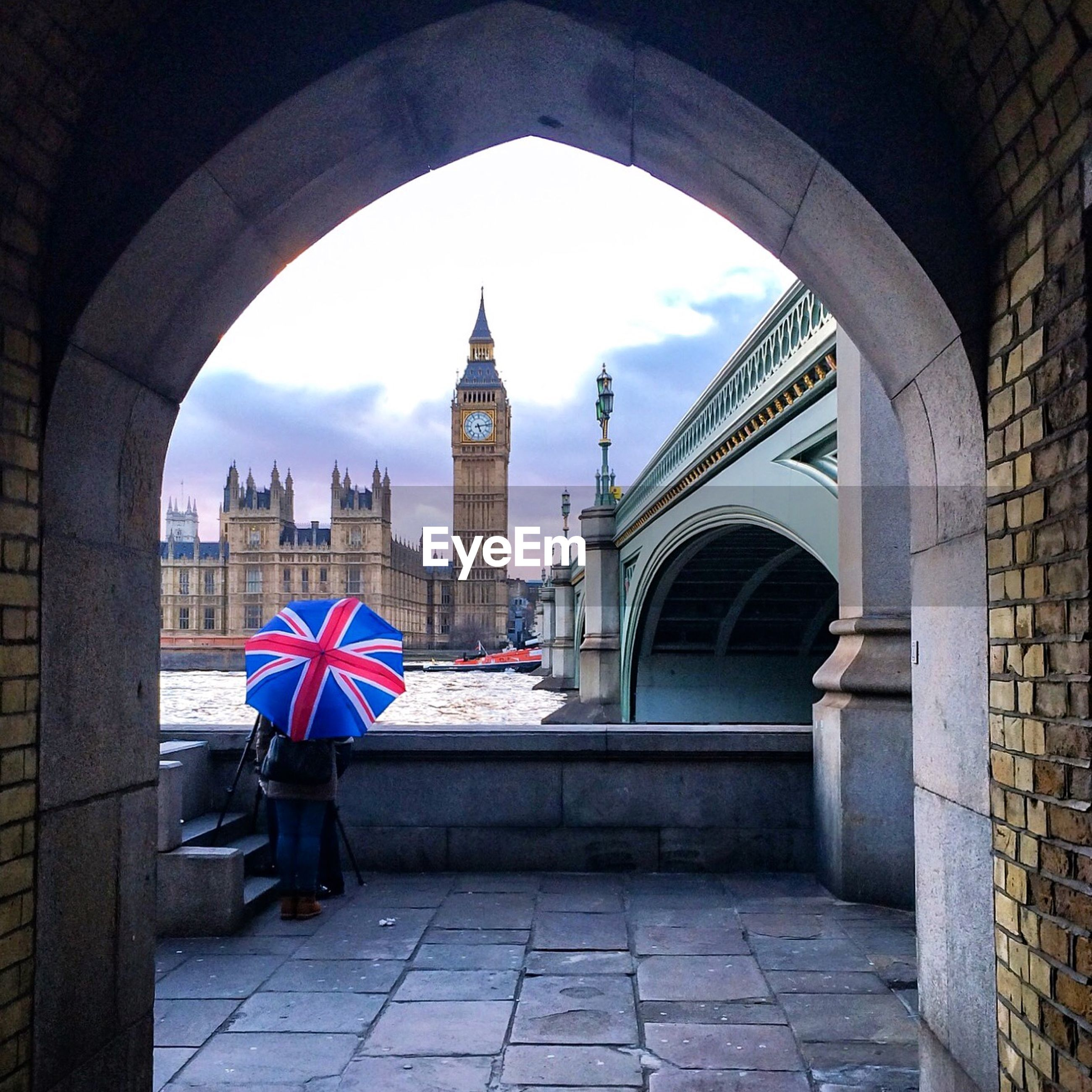 Big ben by river thames seen through archway