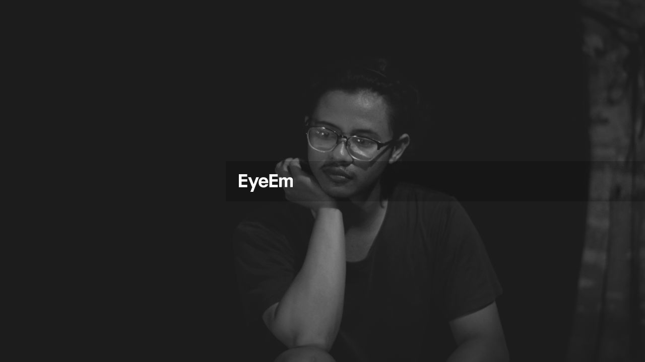 Thoughtful young man wearing eyeglasses sitting against black background