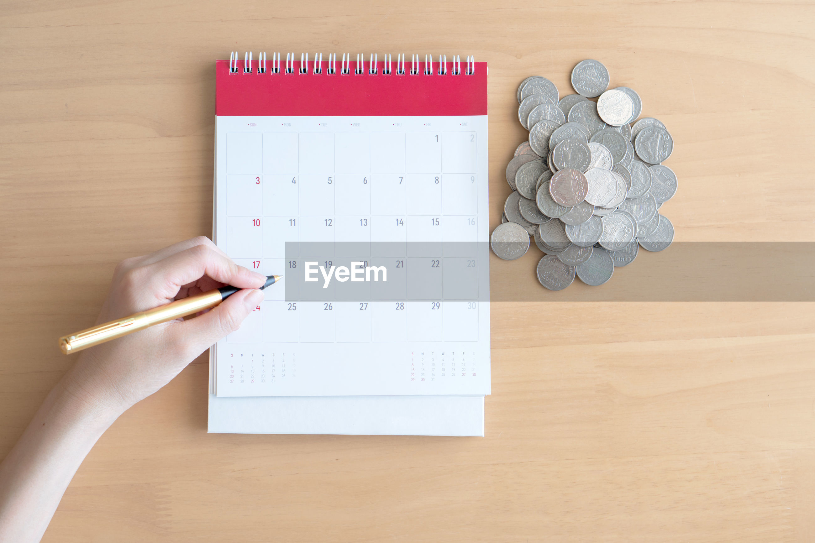 Cropped hand of woman marking on calendar by coins