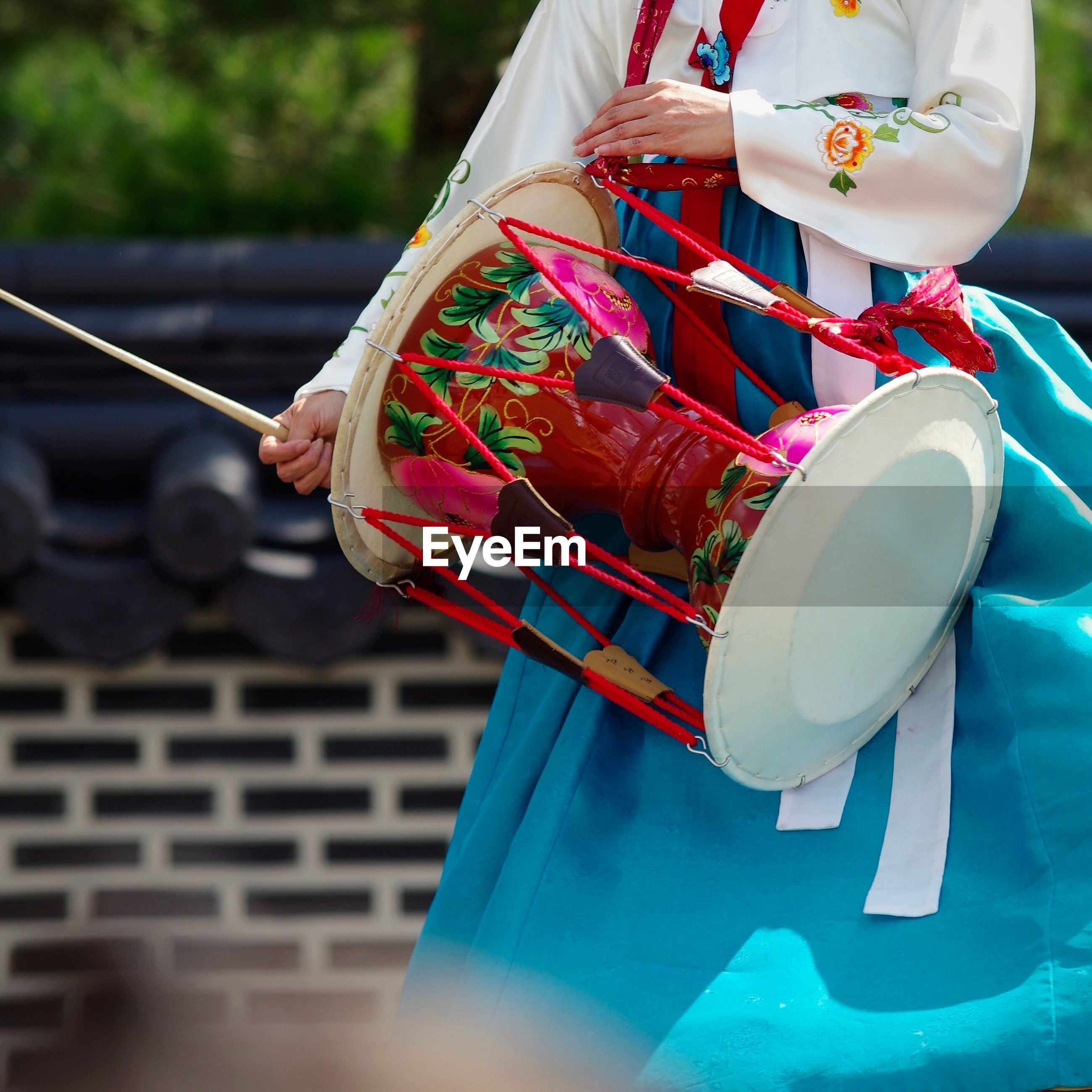 Midsection of woman in traditional clothes banging drum outdoors