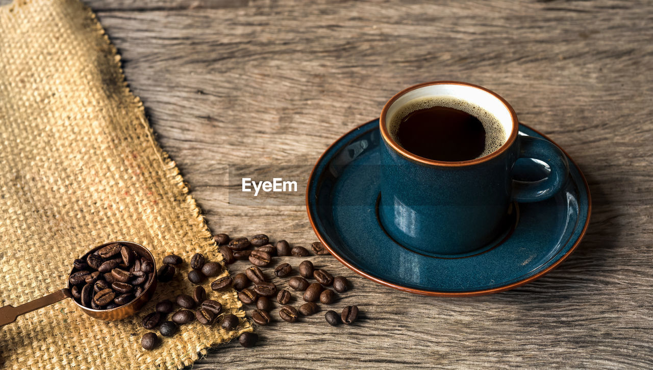 food and drink, drink, coffee, coffee - drink, cup, refreshment, mug, table, wood - material, coffee cup, roasted coffee bean, still life, freshness, indoors, food, high angle view, no people, brown, saucer, close-up, jute, hot drink, caffeine, crockery, black tea, non-alcoholic beverage