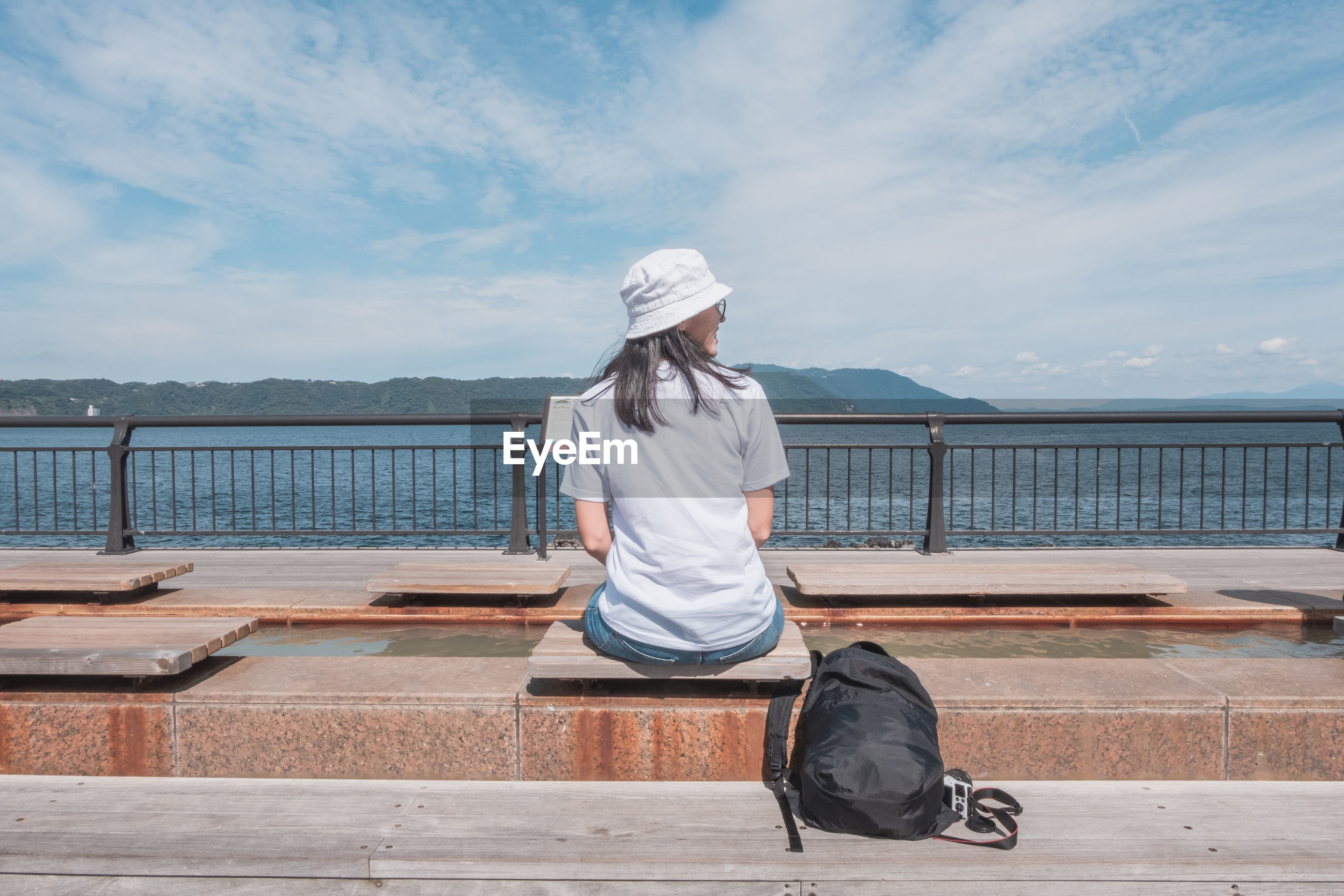 FULL LENGTH REAR VIEW OF WOMAN SITTING ON RAILING AGAINST SKY