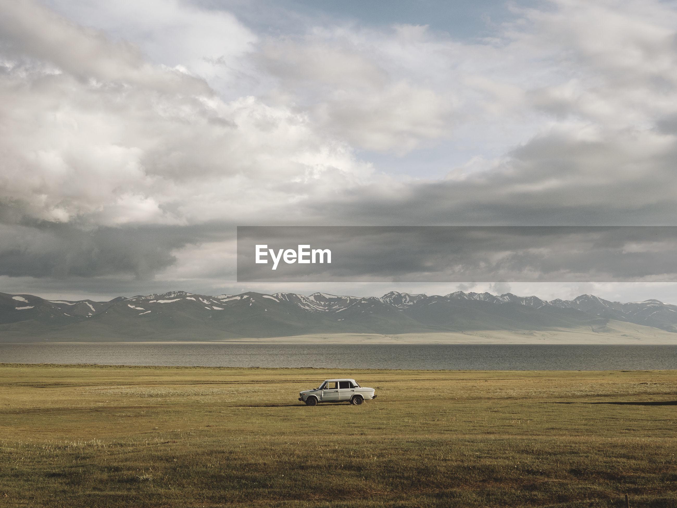 Car on field against cloudy sky