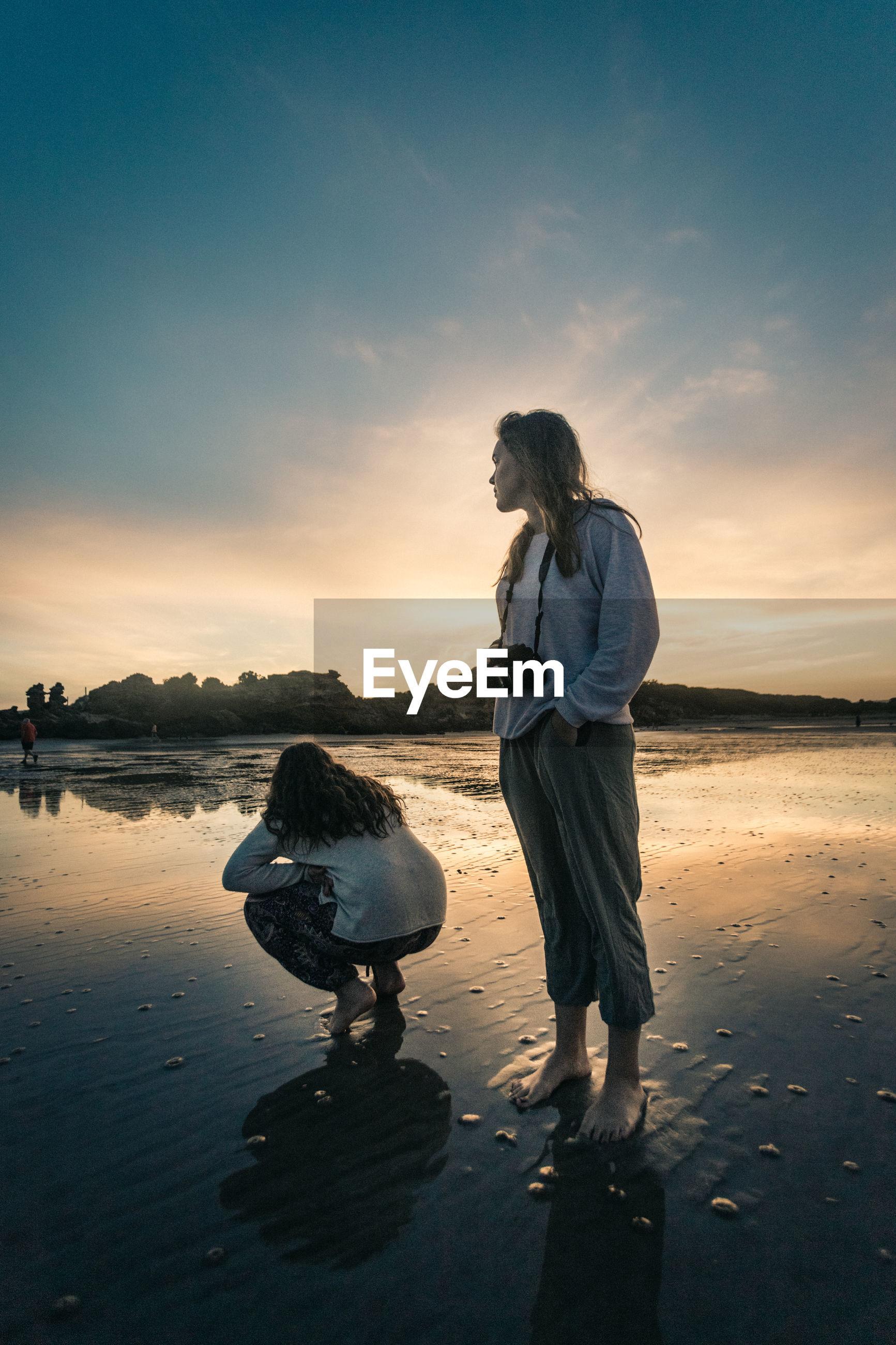 FRIENDS ENJOYING ON BEACH AGAINST SKY DURING SUNSET
