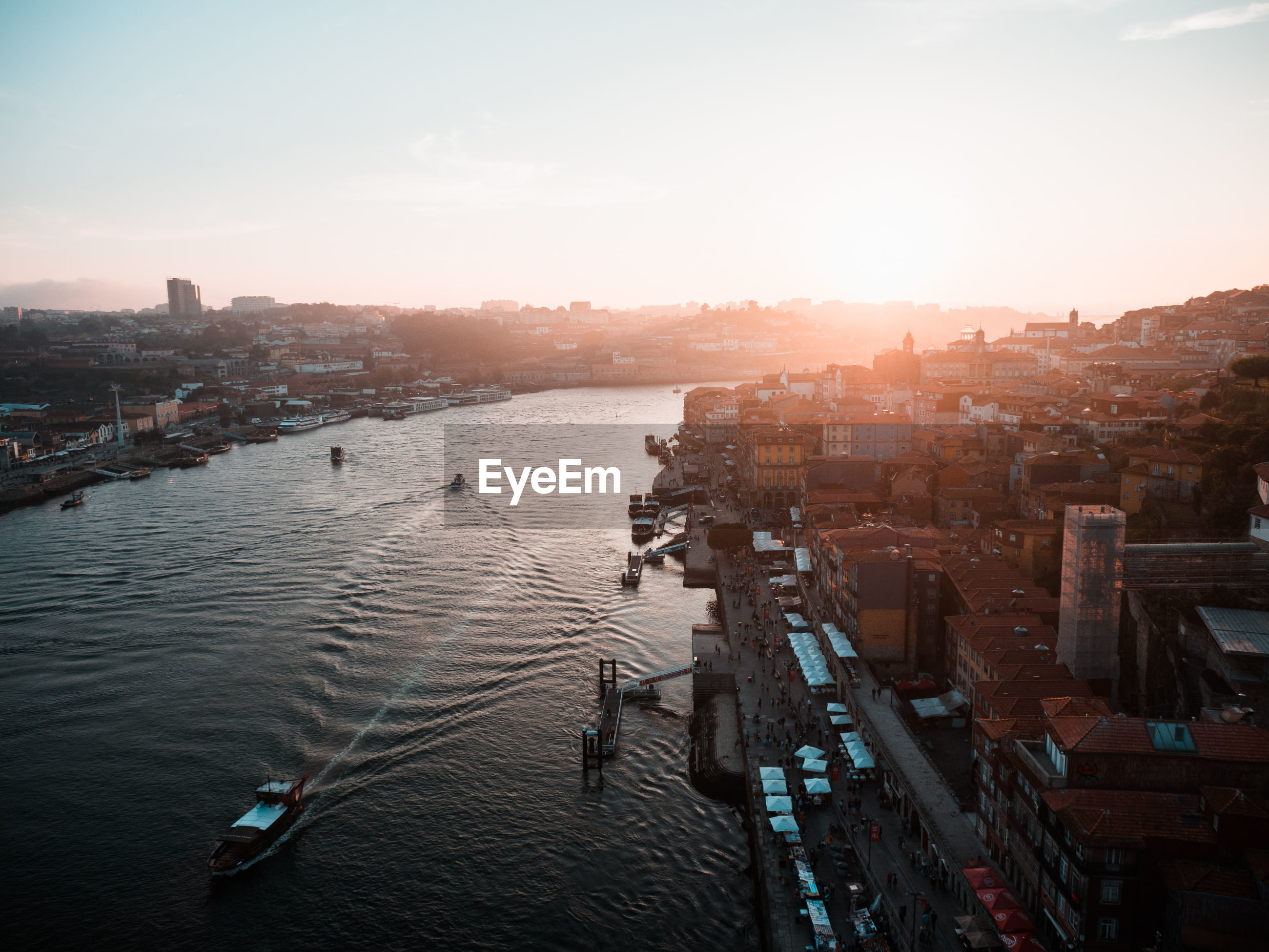 High angle view of city at river during sunset