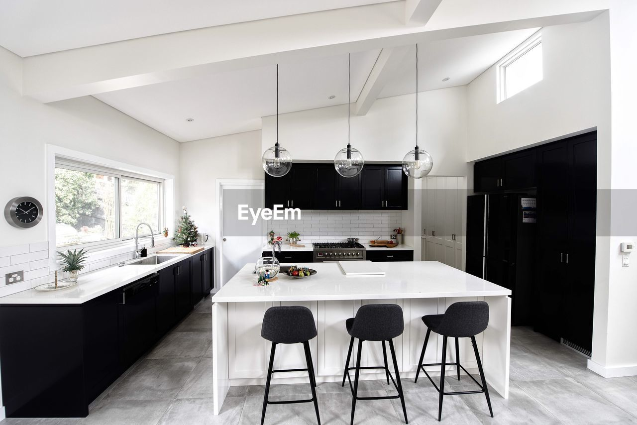 Empty chairs by kitchen island at home
