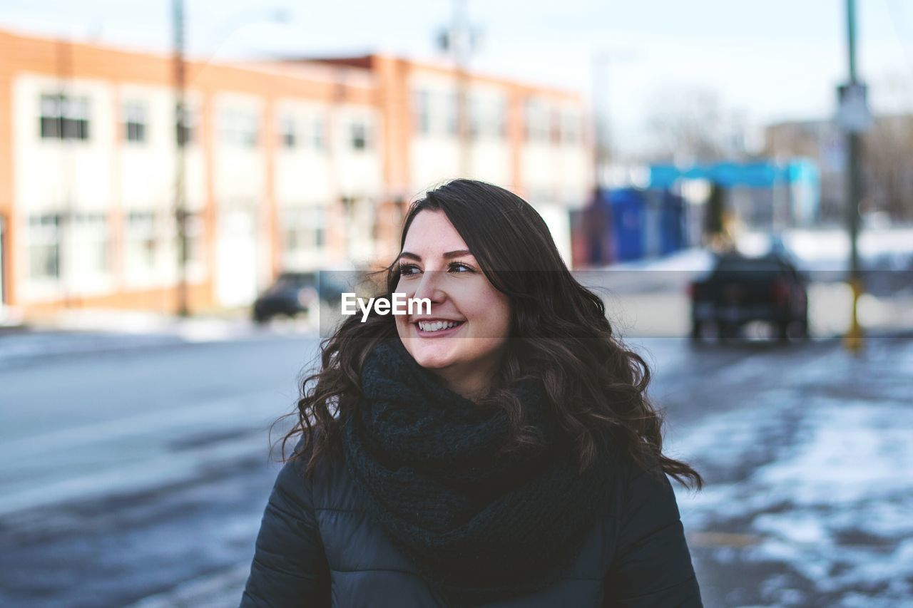Smiling young woman standing on street in city during winter