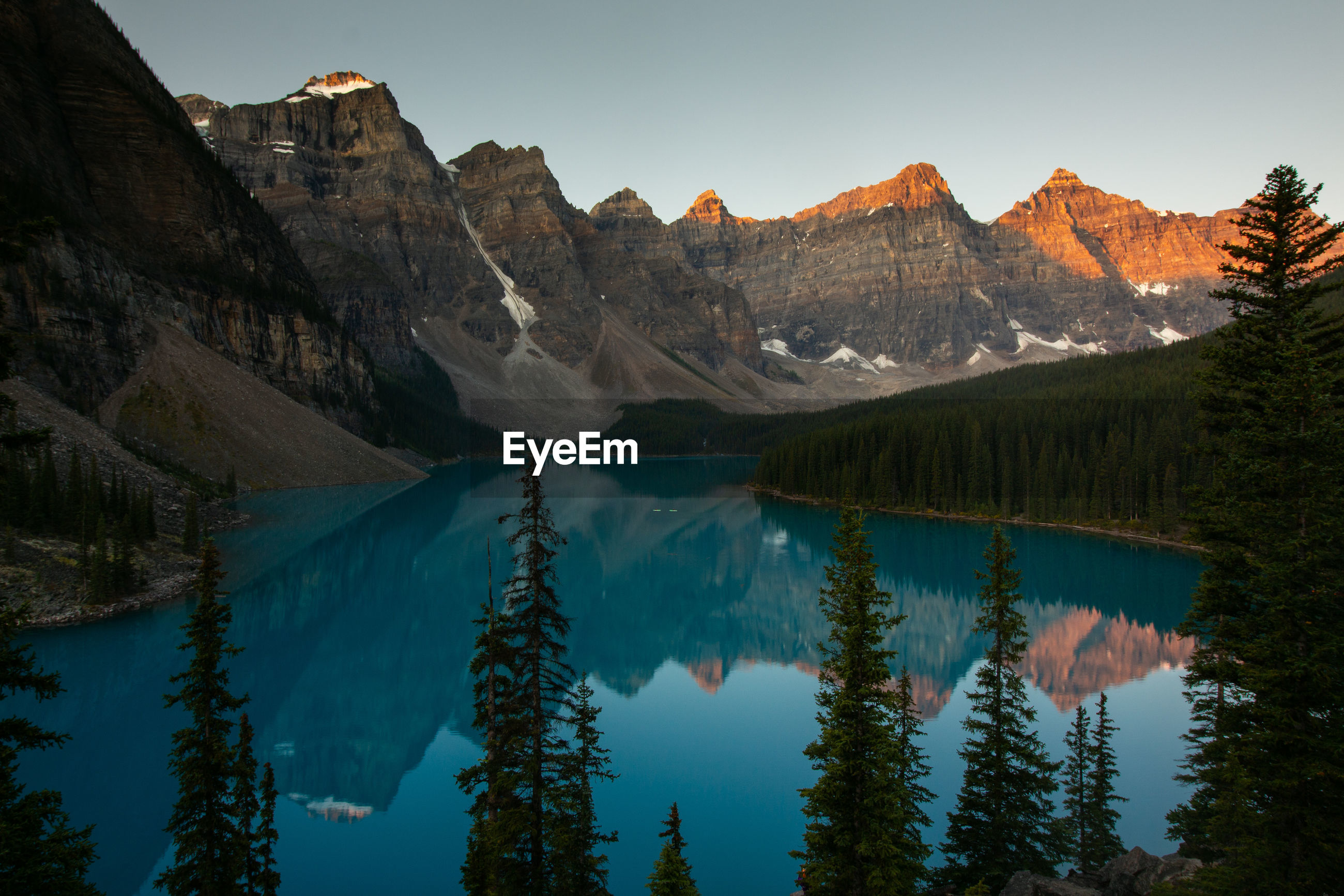 Scenic view of lake and mountains against clear sky during sunset