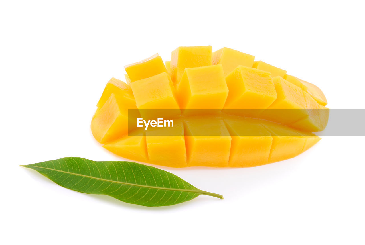 studio shot, white background, still life, food and drink, cut out, yellow, food, freshness, no people, indoors, close-up, plant part, wellbeing, slice, leaf, healthy eating, mango fruit, nature, raw food, sweet food, chopped, snack