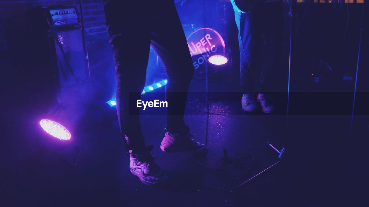 low section, human leg, nightlife, illuminated, nightclub, stage - performance space, night, real people, blue, arts culture and entertainment, performance, standing, leisure activity, men, performing arts event, women, lifestyles, indoors, one person, adult, people