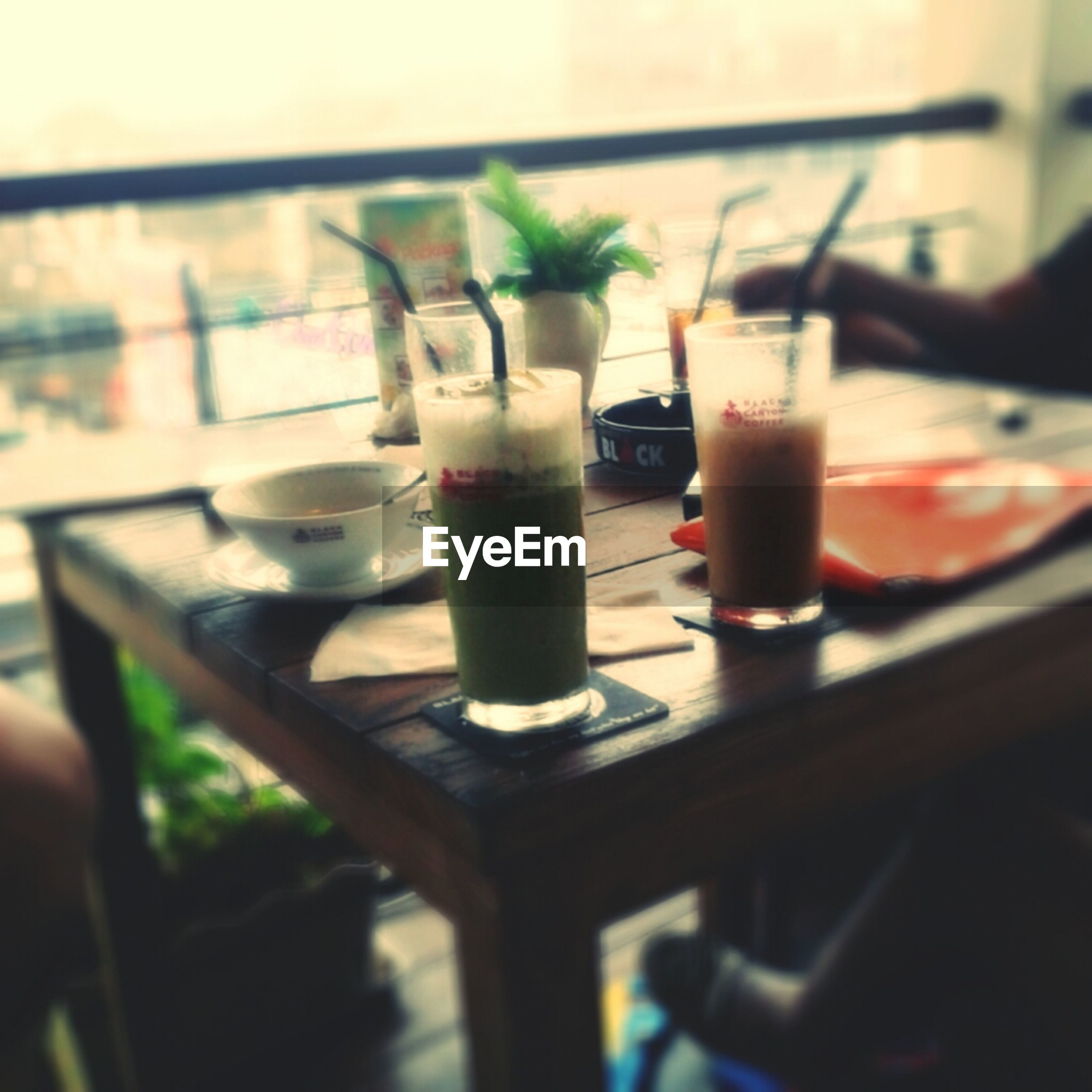 drink, food and drink, table, refreshment, drinking glass, focus on foreground, close-up, indoors, freshness, restaurant, still life, glass - material, selective focus, drinking straw, potted plant, alcohol, glass, no people, cocktail, day