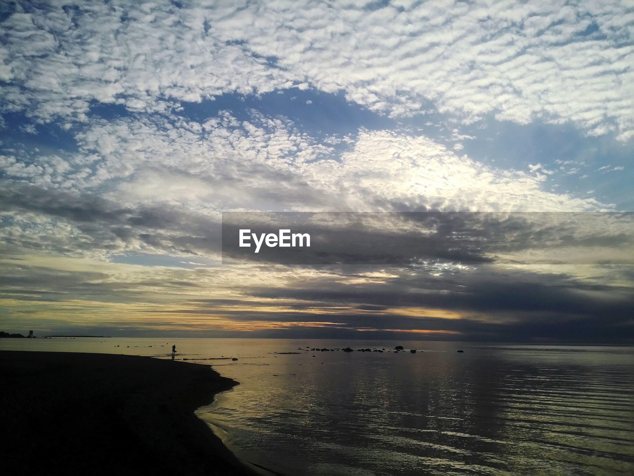 View of calm sea below cloudy sky