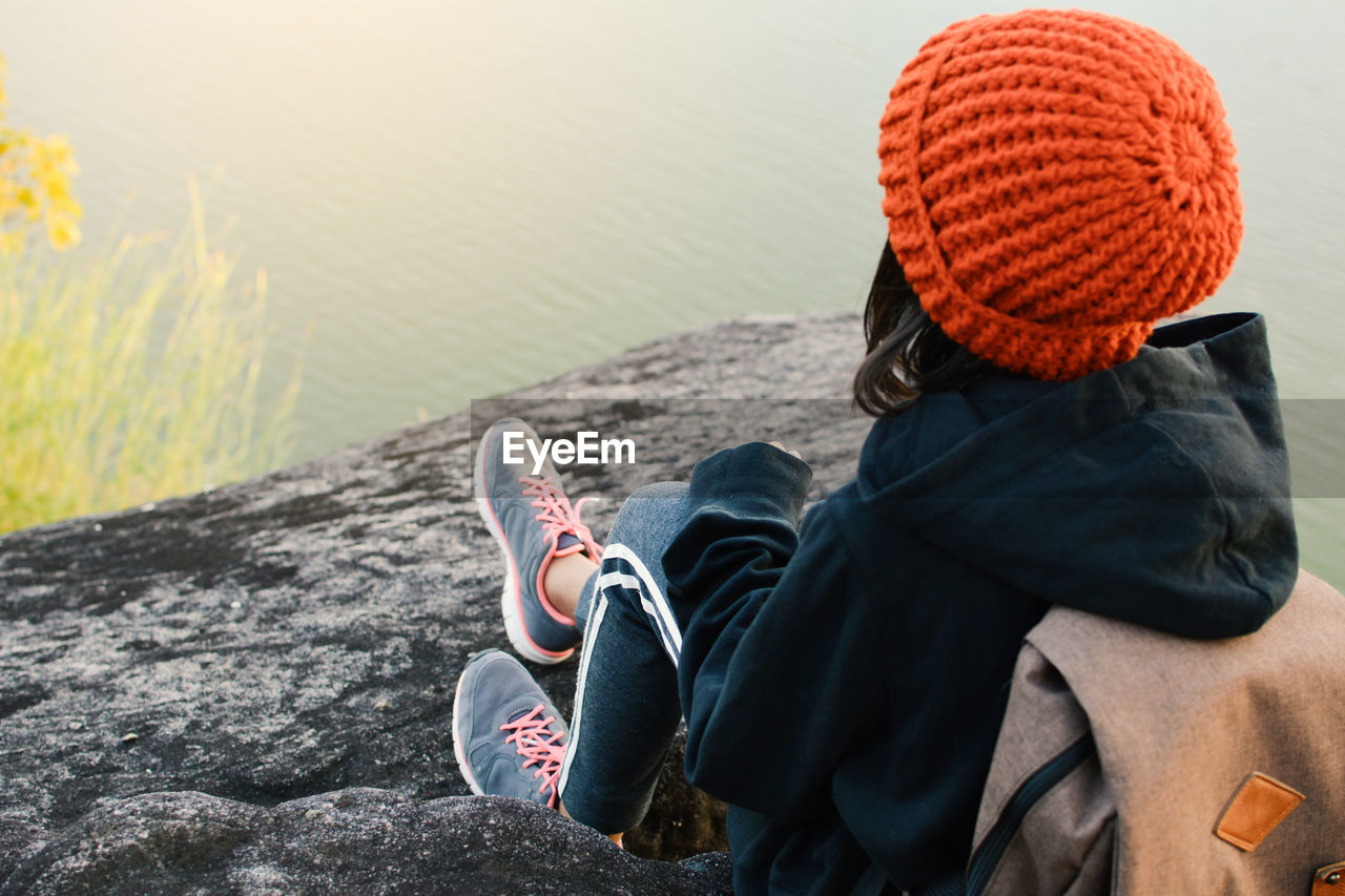 Rear View Of Girl Sitting Against Lake