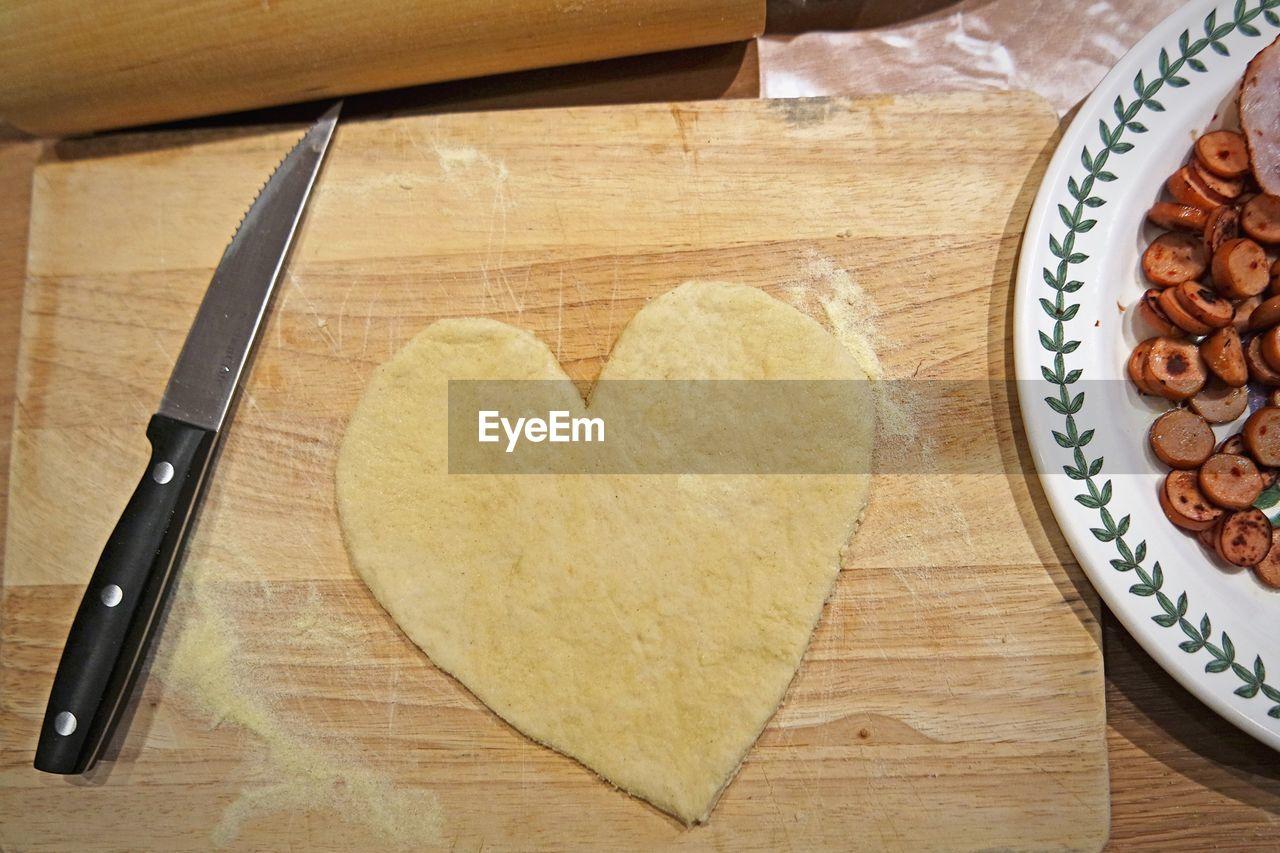 Close-up of heart shape dough on cutting board