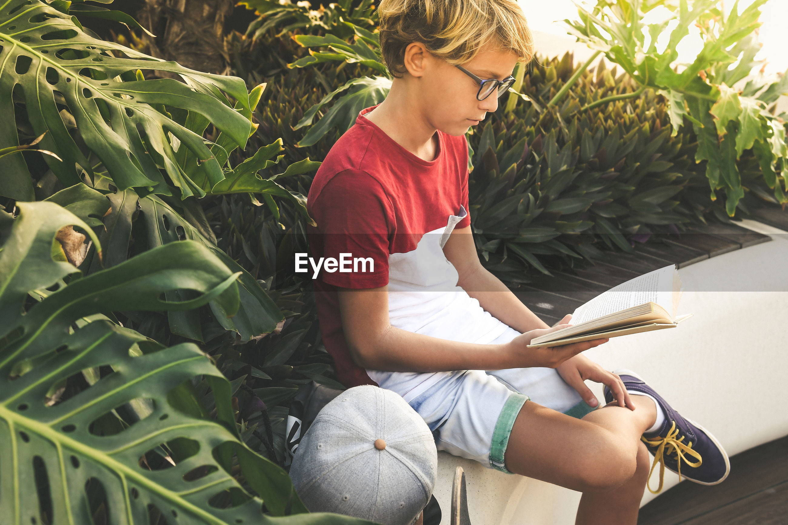 Boy reading book while sitting by plants
