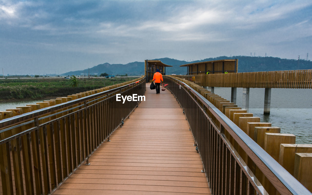 railing, sky, architecture, water, built structure, cloud - sky, real people, the way forward, nature, connection, bridge, direction, lifestyles, scenics - nature, rear view, day, adult, wood - material, beauty in nature, bridge - man made structure, outdoors, footbridge
