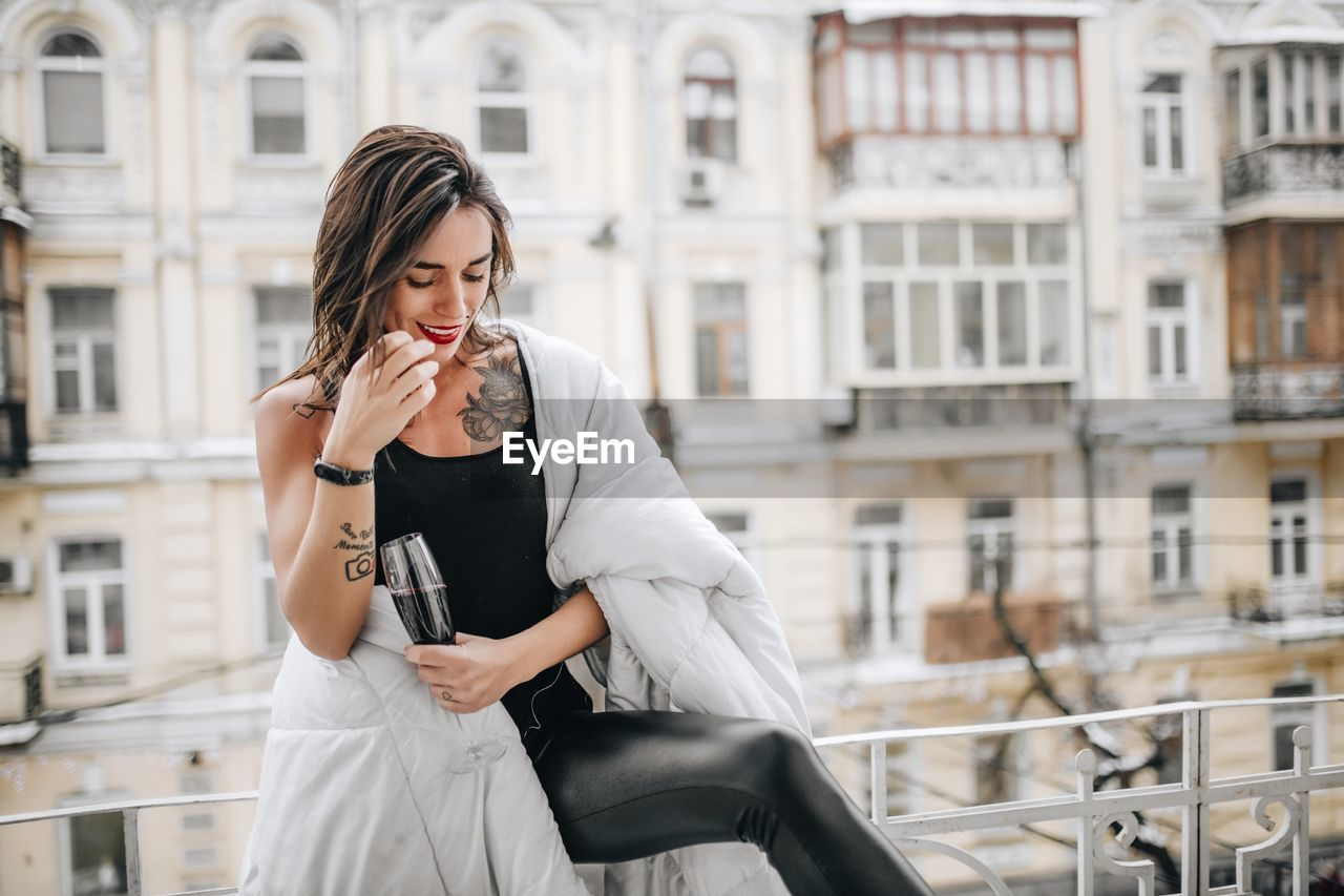 Woman Having Red Wine While Wrapped In Blanket At Balcony