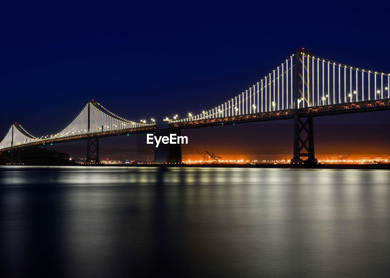 Illuminated San FranciscoOakland Bay Bridge Over River At Night