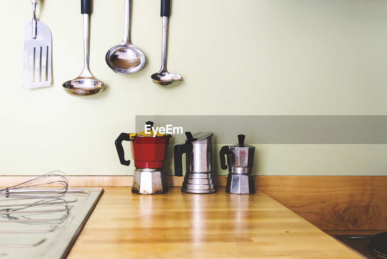 Coffee makers on table by utensils in kitchen